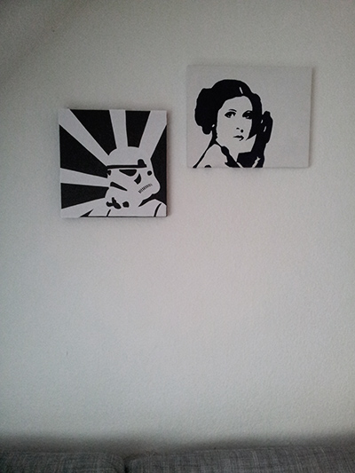 Two black and white Star Wars pictures of a starm trooper and princess Leia hanging on the wall.